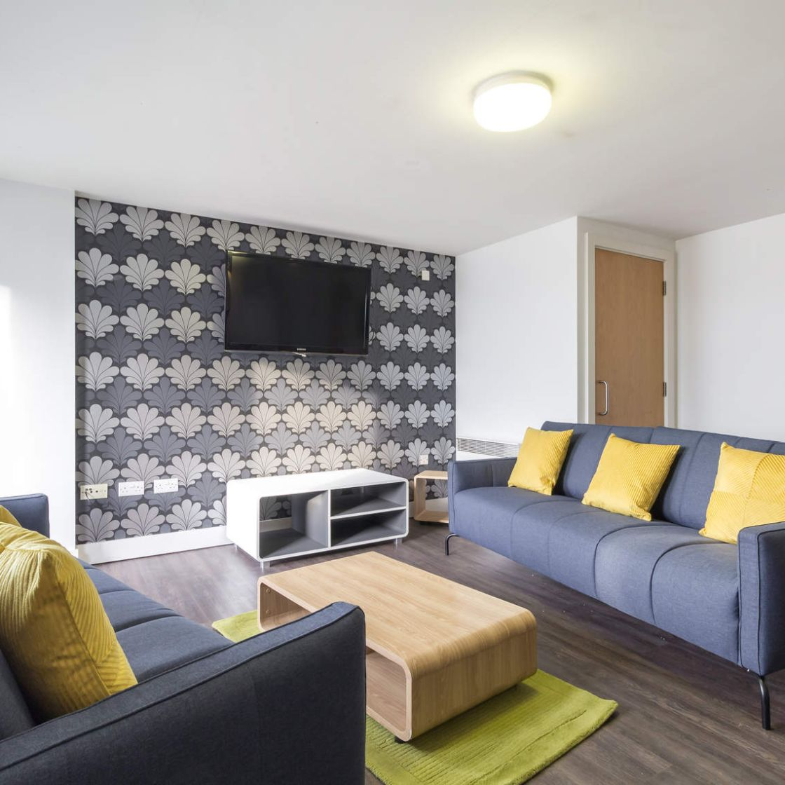 Shared lounge with sofas, coffee table and flat screen TV. Student Accommodation in Leeds. IconInc, Triangle