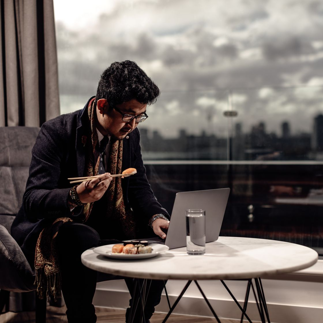 Man eating sushi and working in his apartment. IconInc @ Roomzzz. Student Accommodation in Stratford