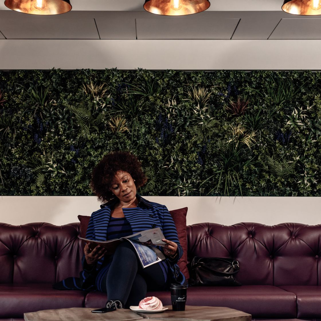 Woman reading in reception lounge with living wall behind her. IconInc @ Roomzzz. Student Accommodation in London