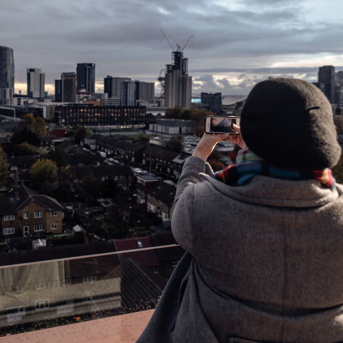 Girl taking photo of London skyline from balcony. Student Accommodation in London