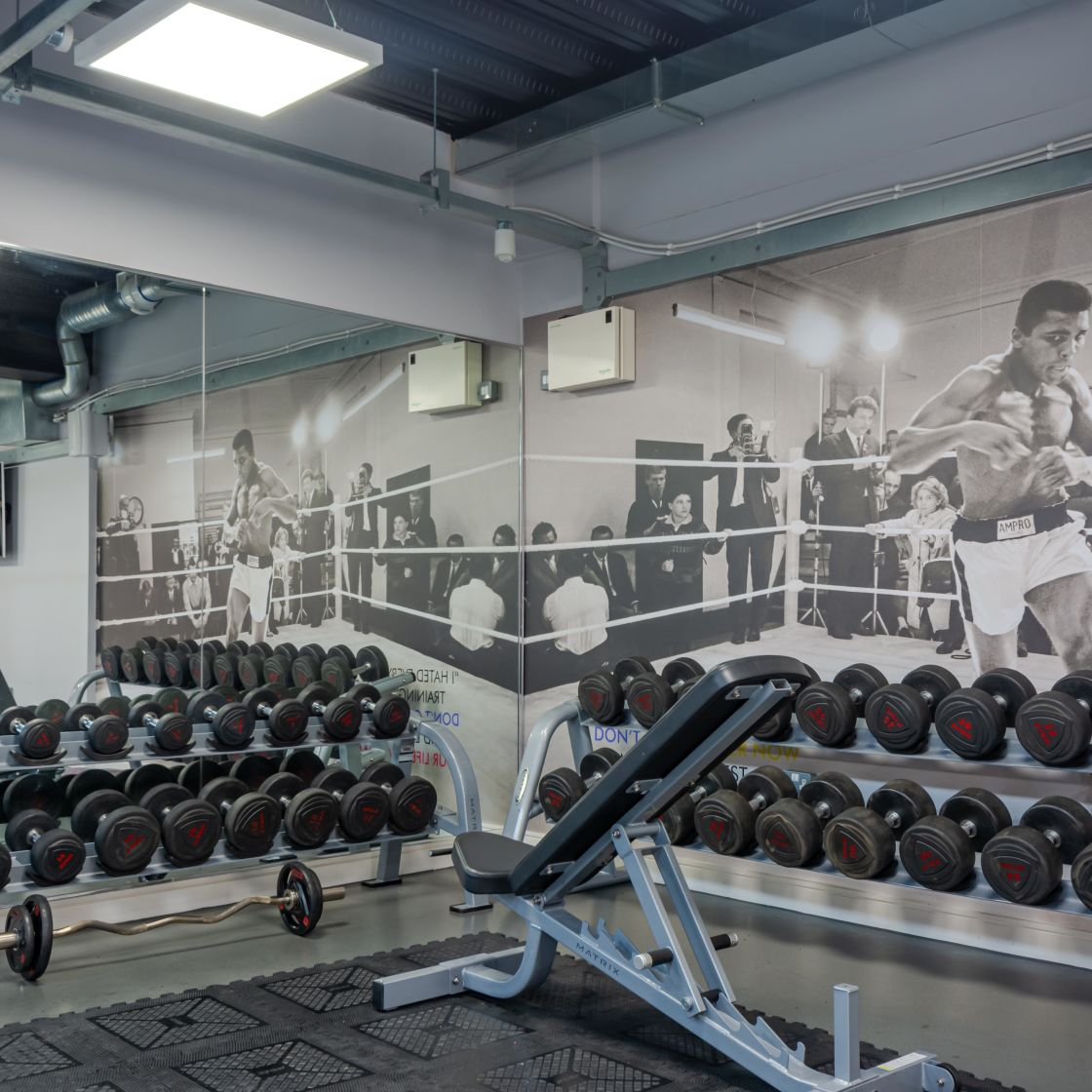 Gym with free weights and bench at IconInc, The Glassworks. Student Accommodation in Leeds