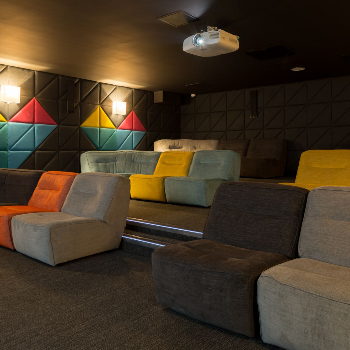 Cinema room with soft fabric seating at IconInc, The Glassworks. Student Accommodation in Leeds