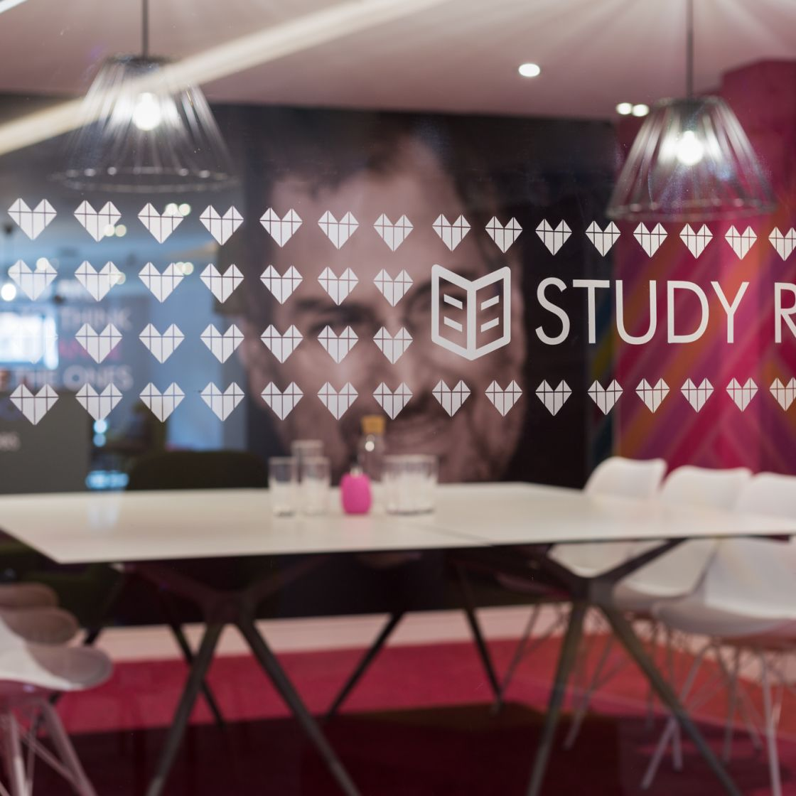 Pink private study room with desk and seating at IconInc The Glassworks. Student Accommodation in Leeds