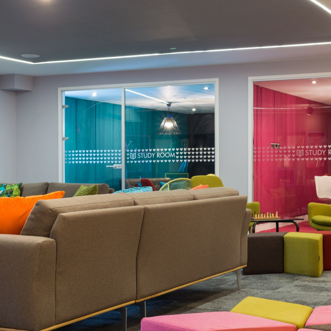 Reception and area with sofa and private study rooms at IconInc, The Glassworks. Student Accommodation in Leeds