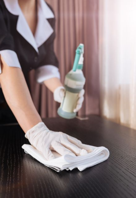 Housekeeper cleaning with disinfectant