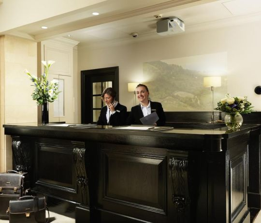 Concierge behind reception desk. Student Accommodation in London