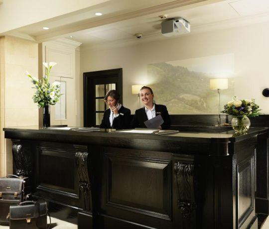 Hosts behind a reception desk