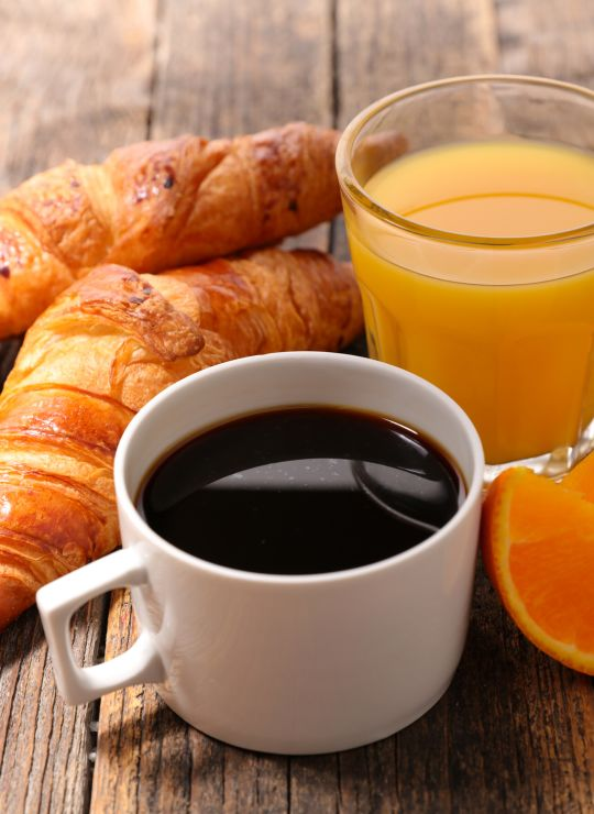 Breakfast spread with coffee, pastries fruit and juice.