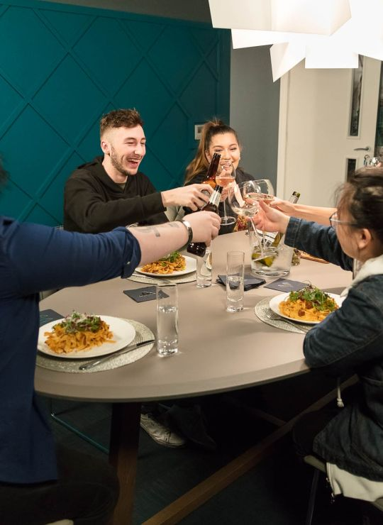 Students eating dinner in the private dining room at IconInc, The Ascent. Student Accommodation in Liverpool