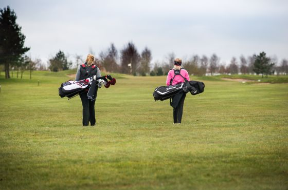 Ellie and golfer walking on the green at Leeds Golf Centre