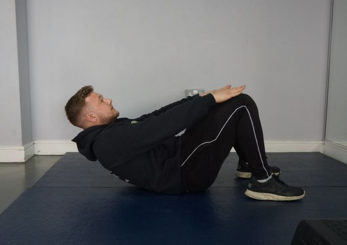 A personal trainer performing a simple bridge exercise for circuit training beginners