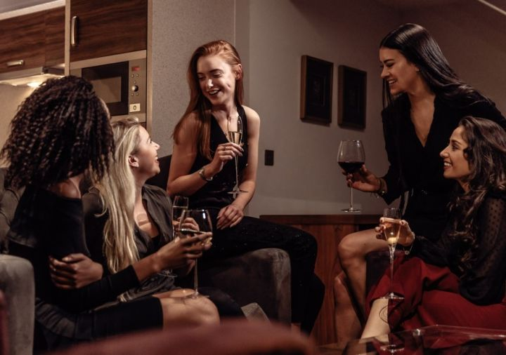 A group of women drinking together in their serviced apartment at Roomzzz.