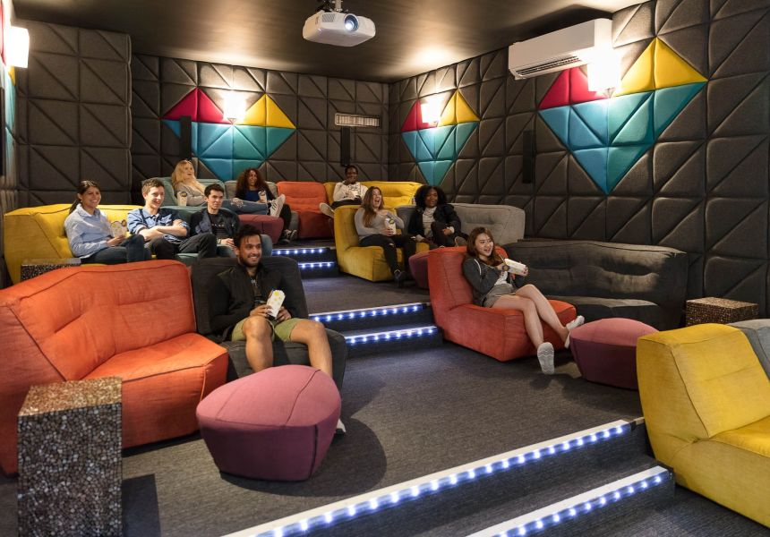 Students eating popcorn in the Cinema at IconInc. Student Accommodation in Leeds