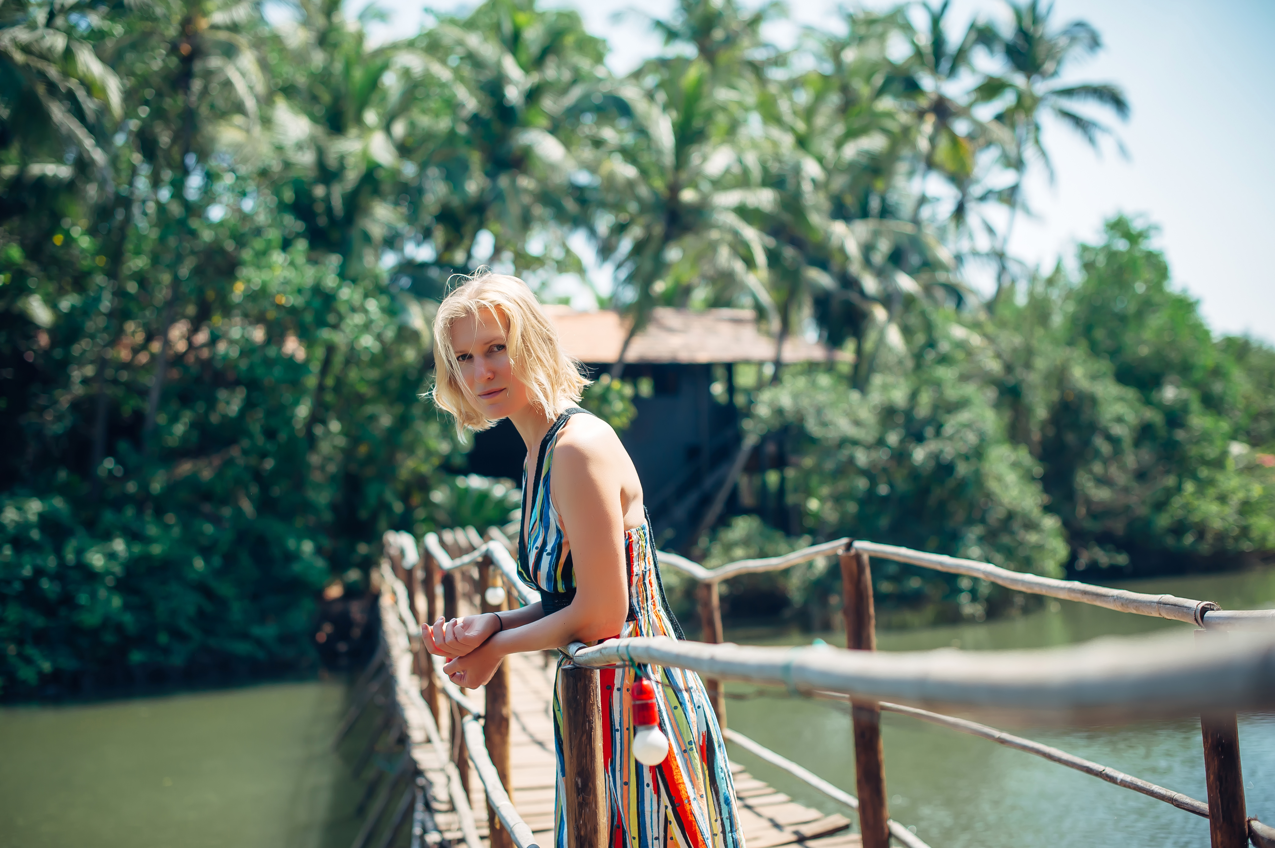 A woman on a bridge in front of the jungle smiles.jpg