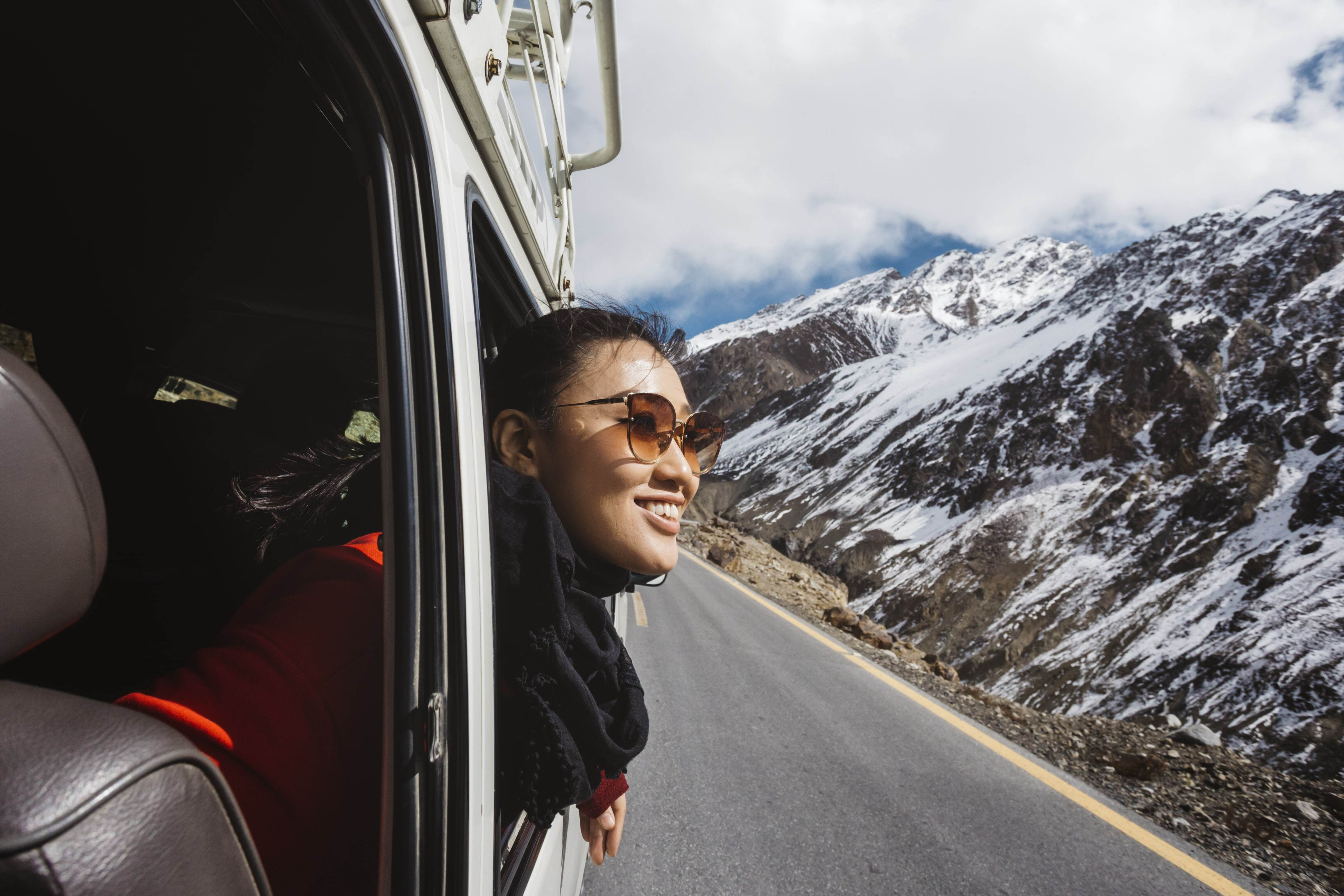 A woman stares at the landscape around her in a van with sunglasses on while smiling.jpg