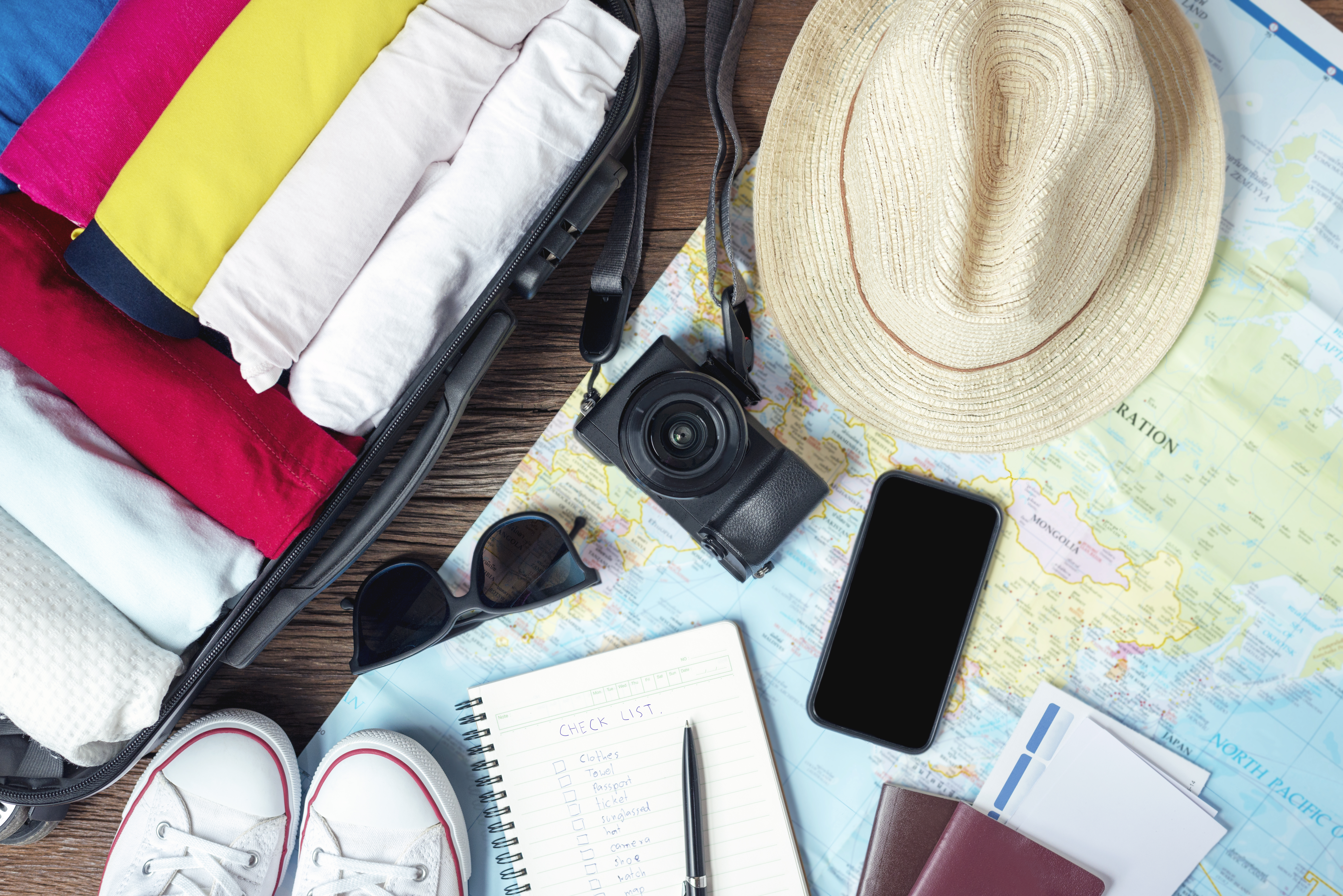 prepare-accessories-and-travel-items-for-new-journey-packing-clothes-in-suitcase-bag-on-wooden-board.jpg