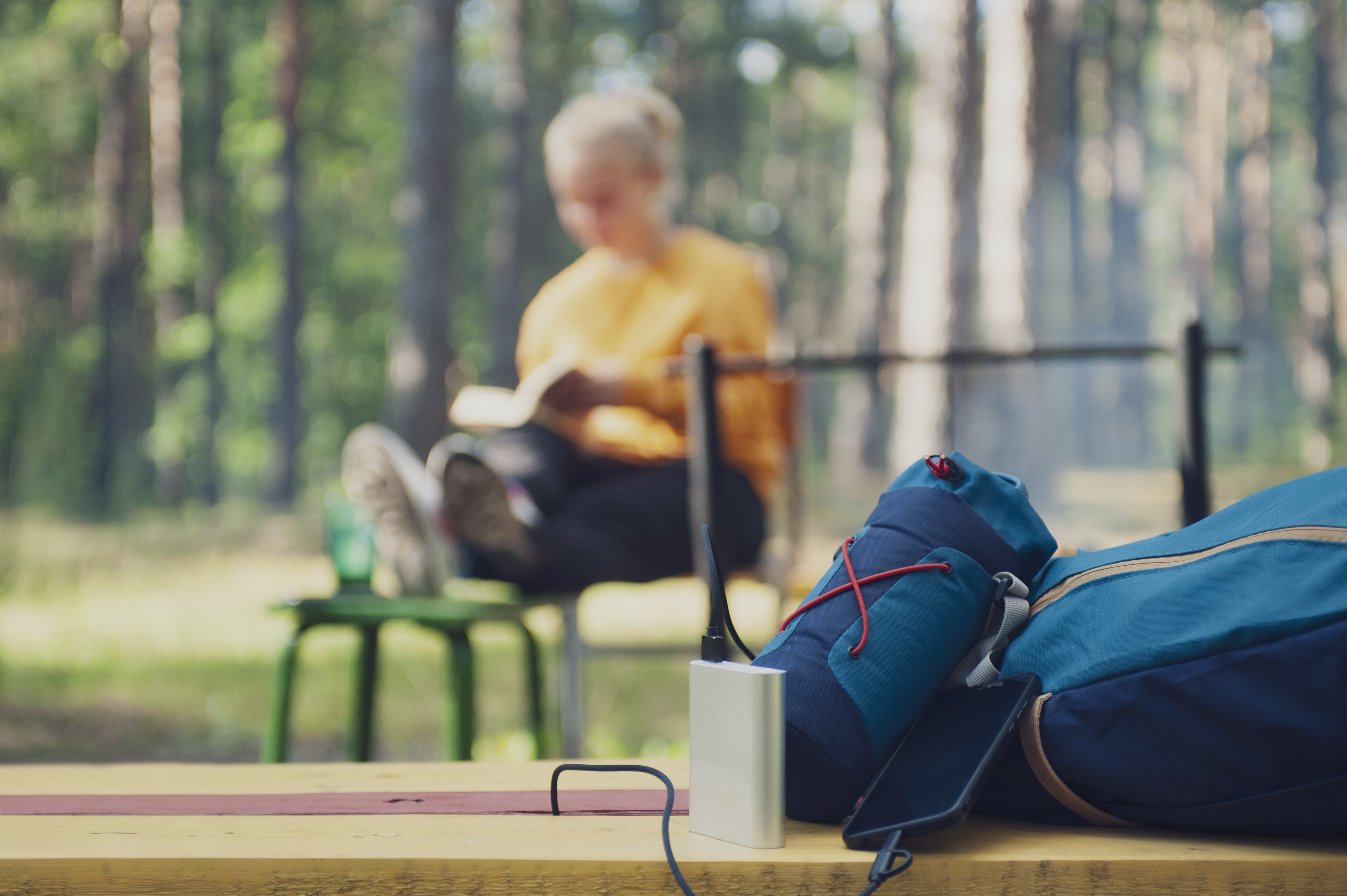 portable-charger-in-camping-girl-tourist-reading-book-in-the-woods-on-the-background-of-backpack-and-bank-turn.jpg