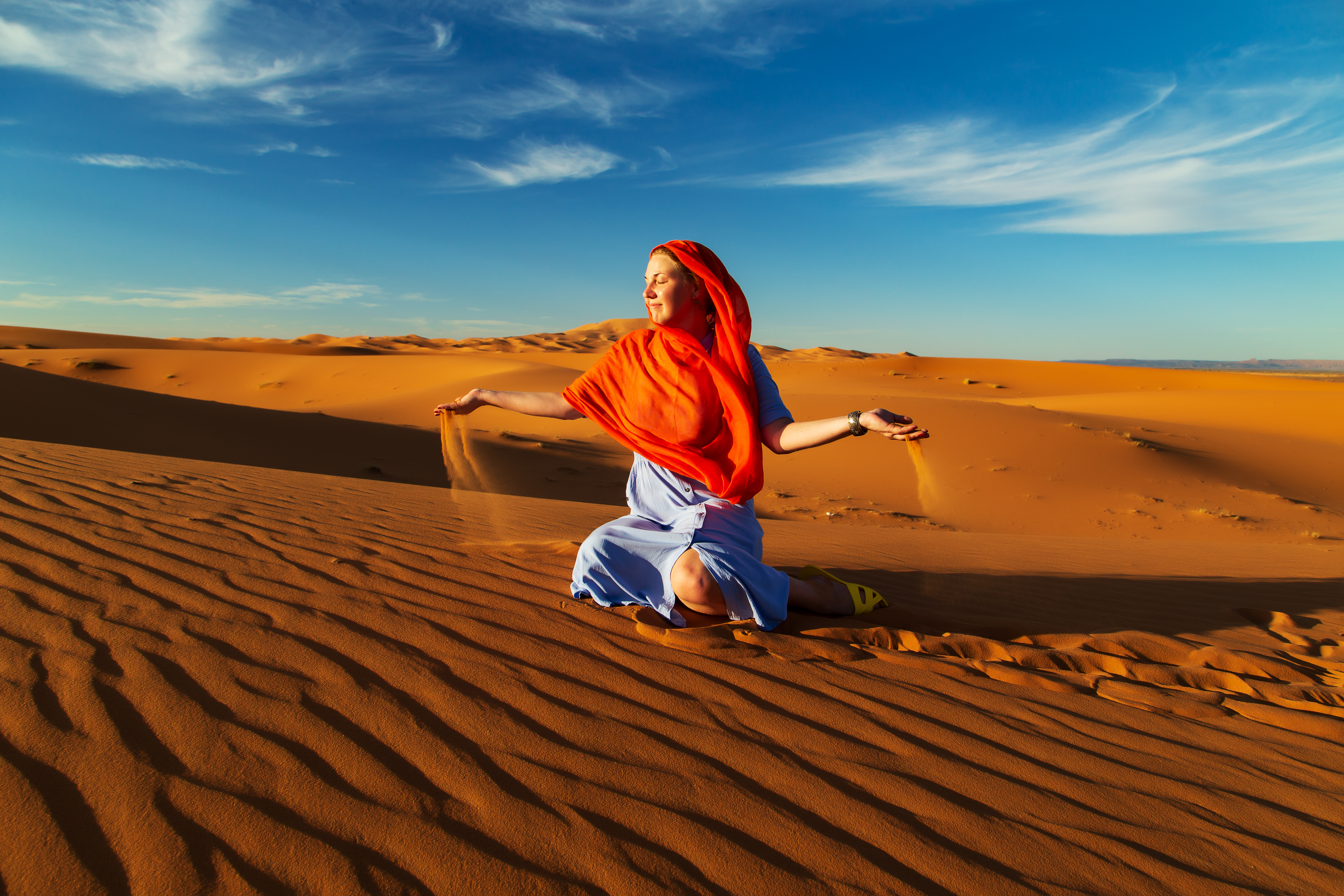 A woman in the desert plays with sand.jpg