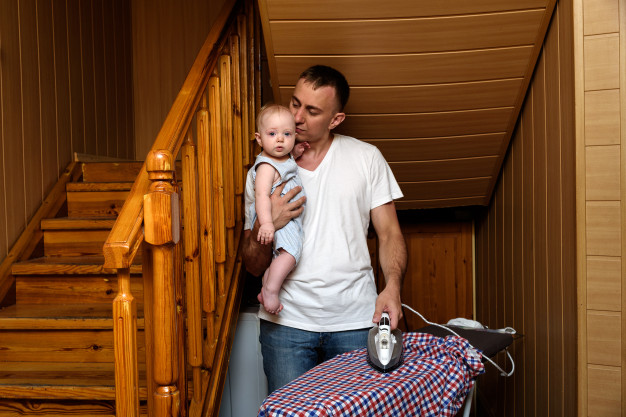 A dad holding his baby and an iron.jpg