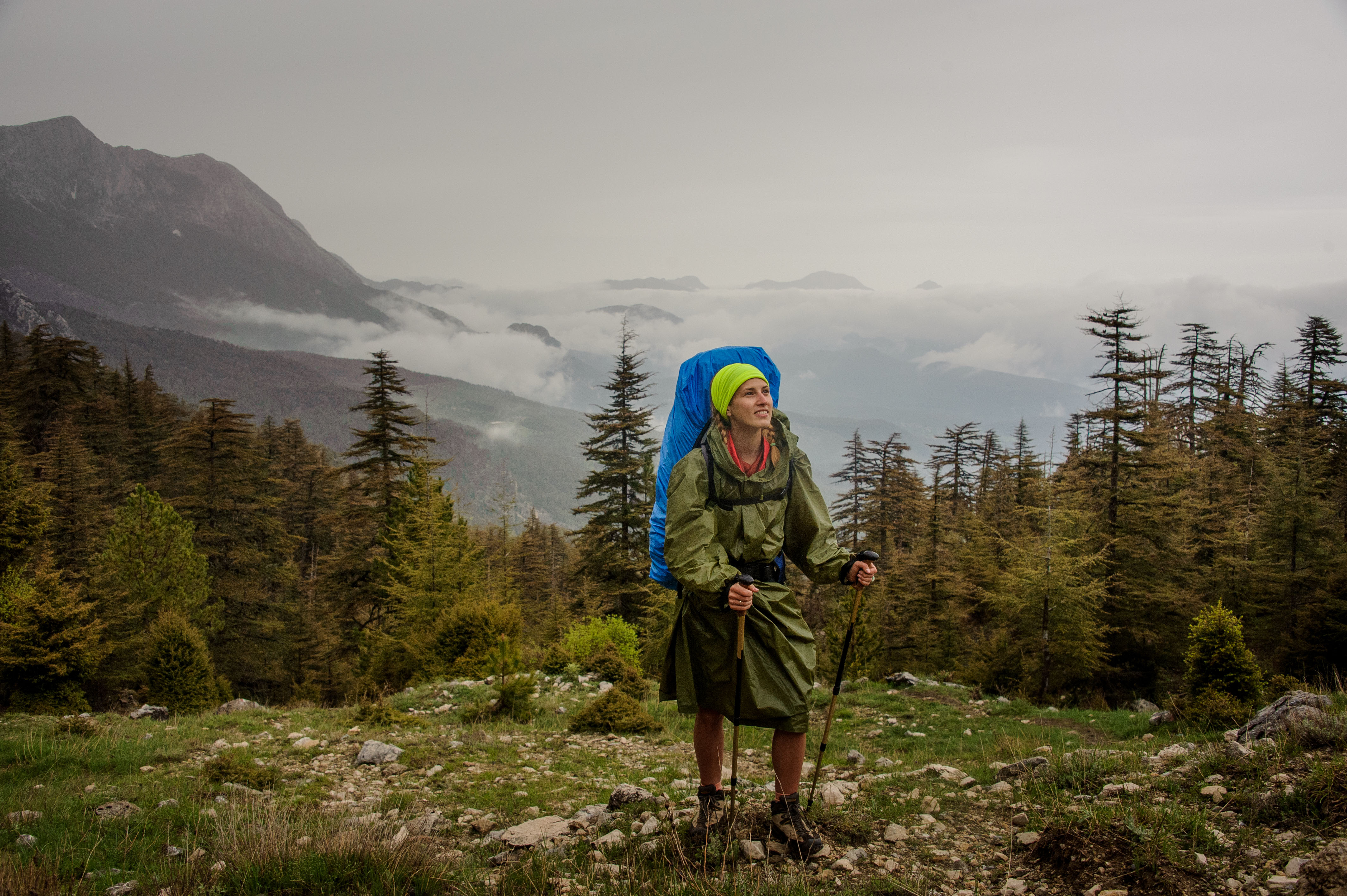 Une voyageuse solo est en montagne avec un sac à dos sous la pluie.jpg