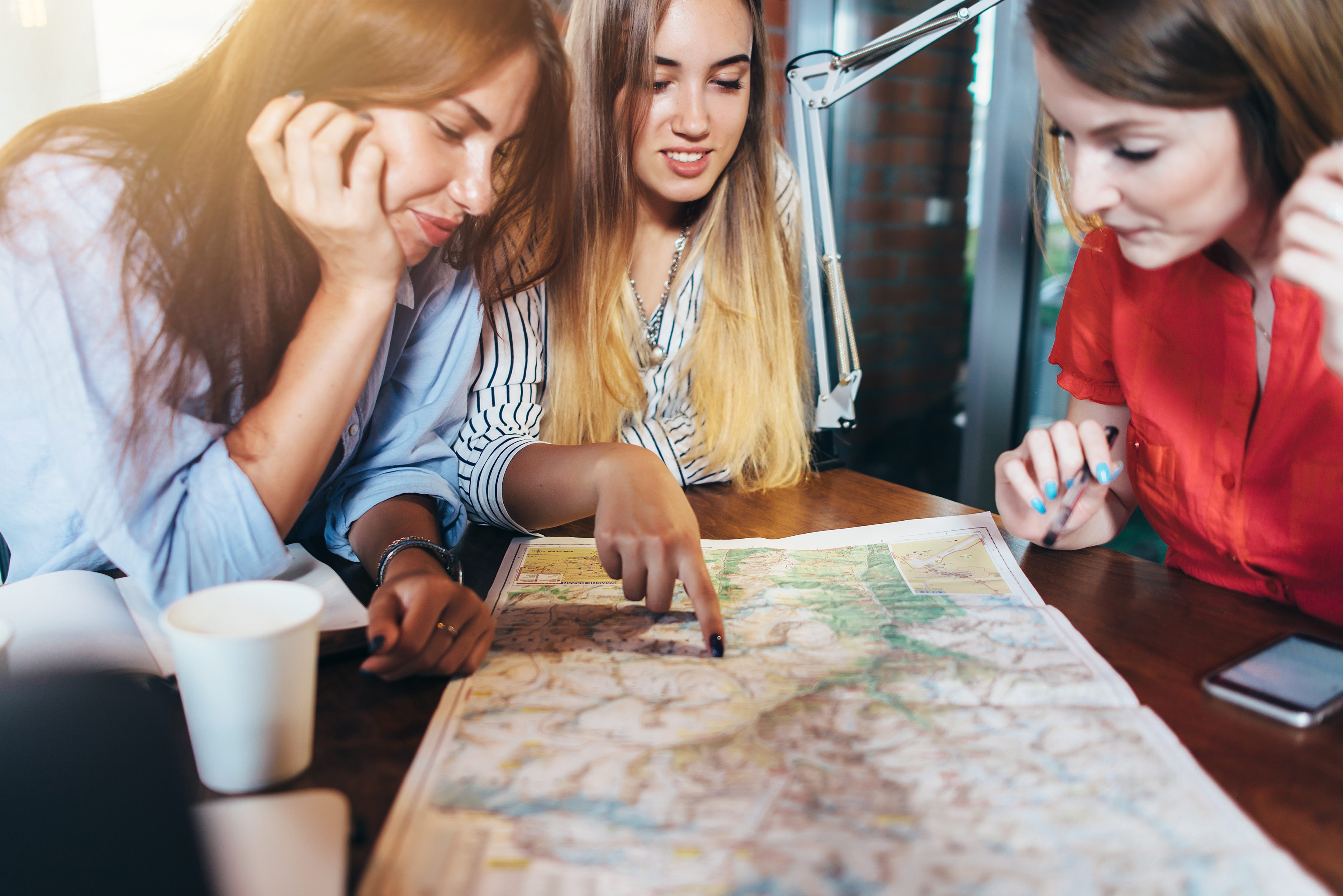 three-girlfriends-planning-their-vacation-sitting-at-table-around-map-choosing-the-destination.jpg