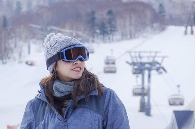 A woman is at the botttom of a ski road surrounded by snow with a ski mask and a hat.jpg