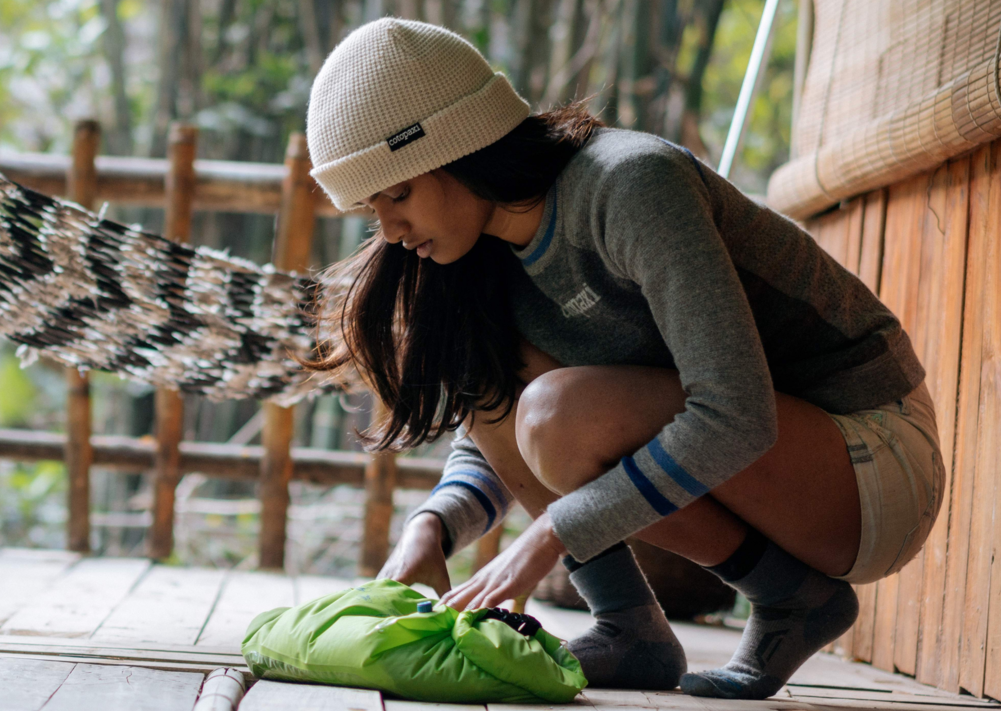 A woman is tying a green bag on the floor.png