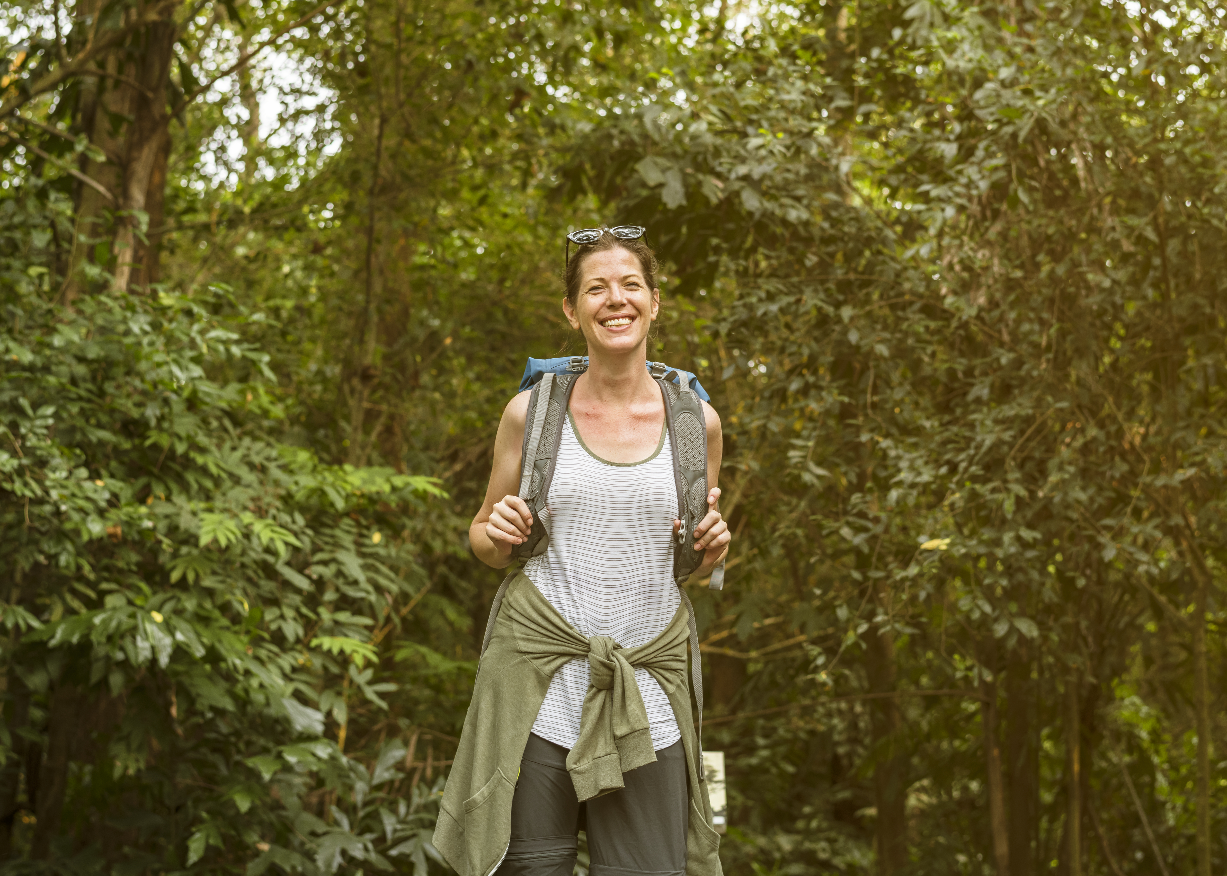 A solo female traveler smiling in a forest with her backpack.jpg