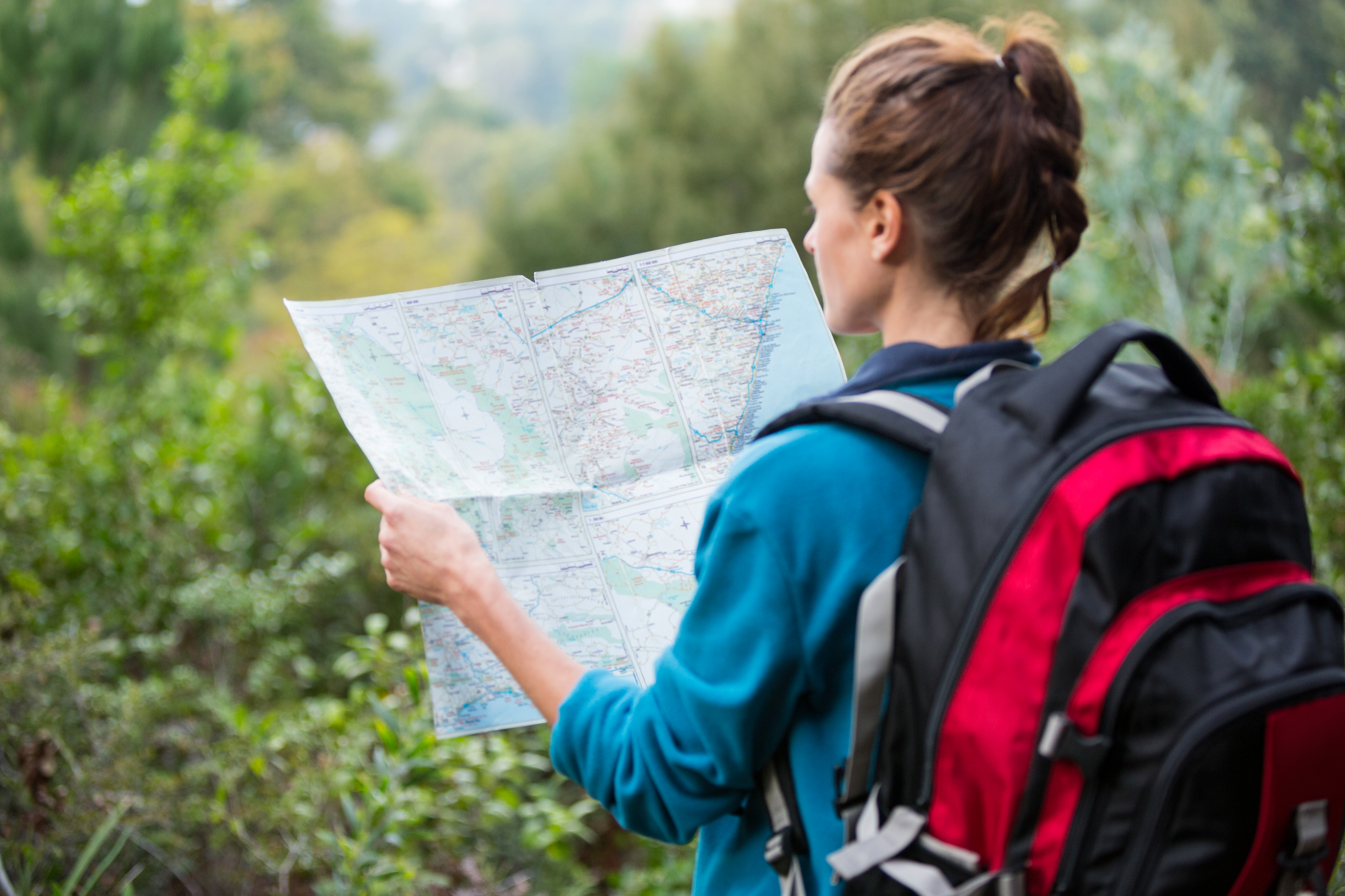 A woman from behind is consulting a map with a red backpack.jpg