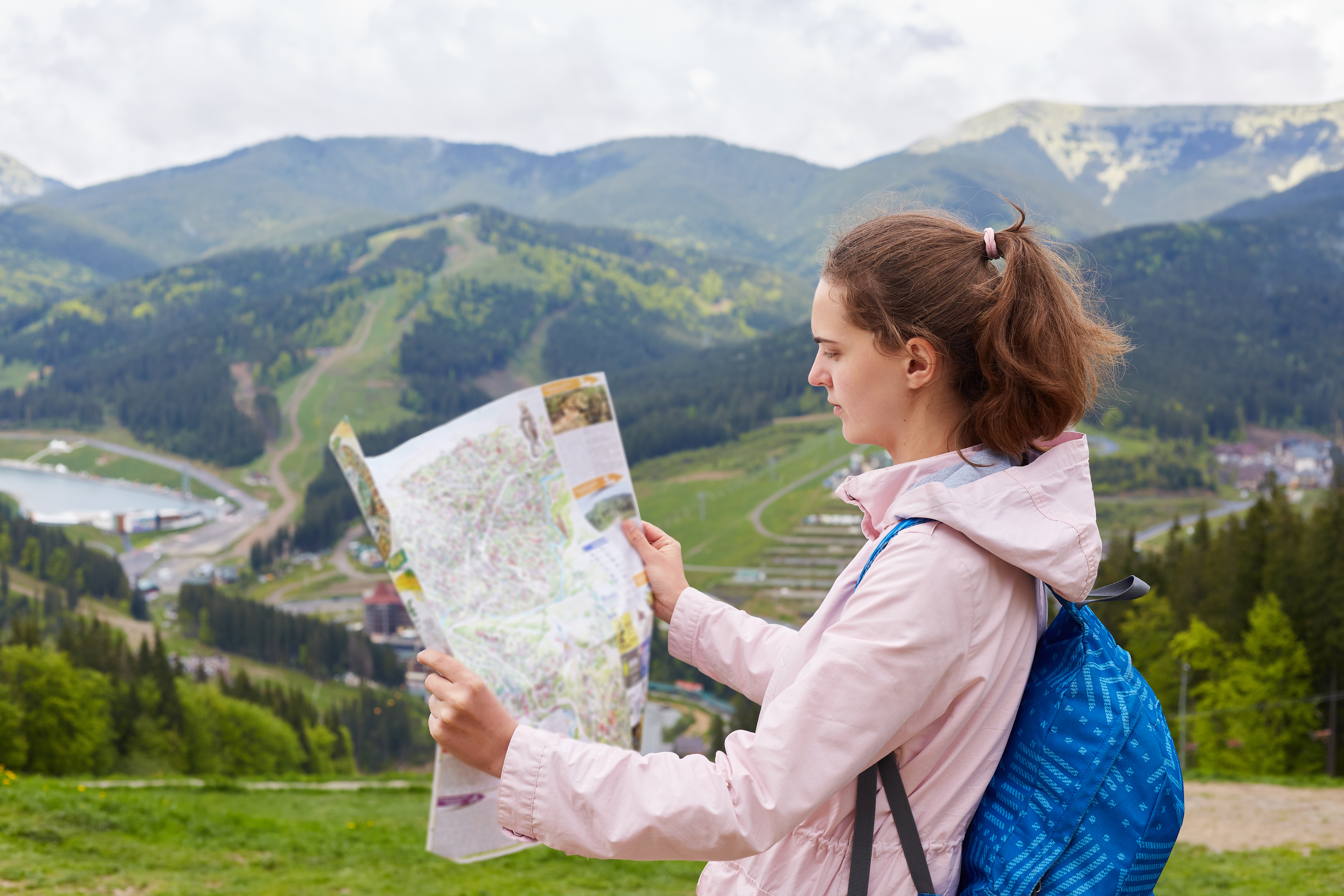 profile-of-attractive-young-tourist-being-lost-on-her-way-looking-at-map-attentively-searching-for-proper-route-standing-at-hill.jpg