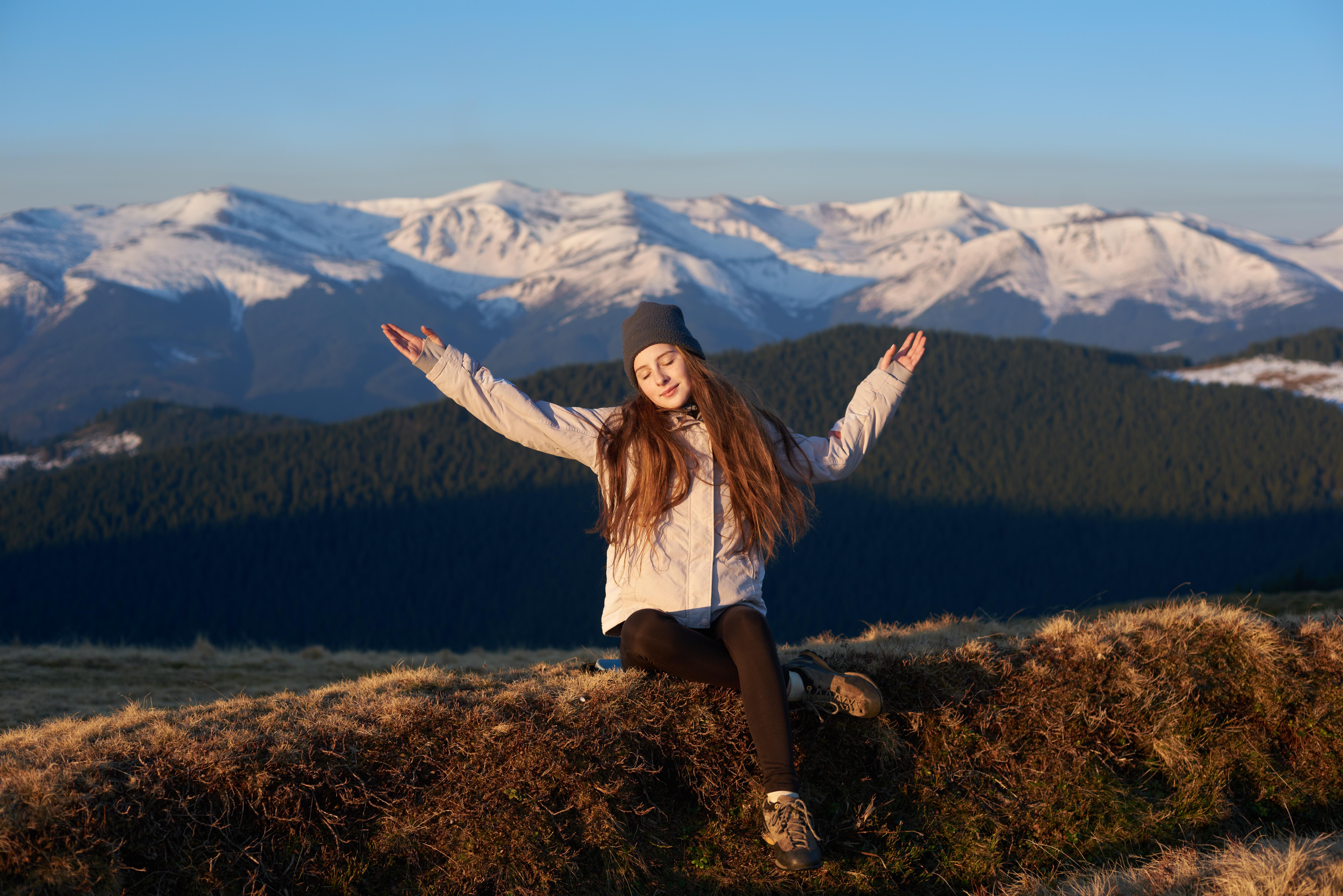Une femme lève les bras au ciel en souriant devant un paysage de montagnes.jpg