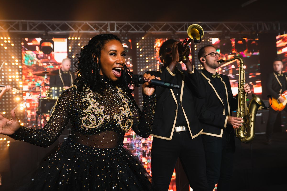 Jam Hot singer & horns perform Crazy In Love wearing dapper gold outfits