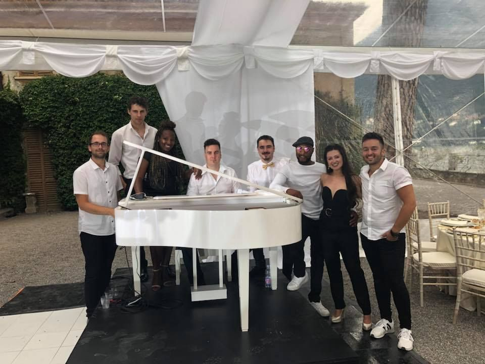 Jam Hot huddle around a White Grand Piano at a Wedding