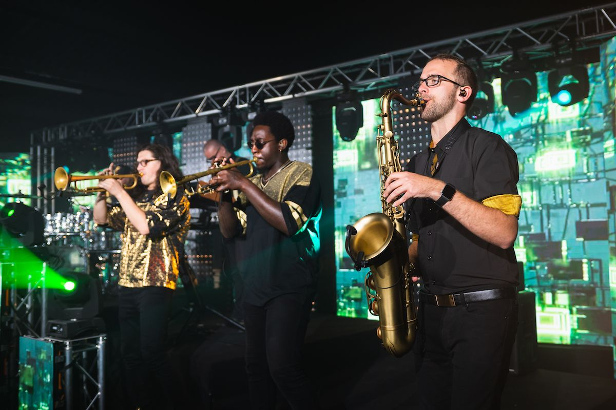Jam Hot Horn Section on stage with green backdrop