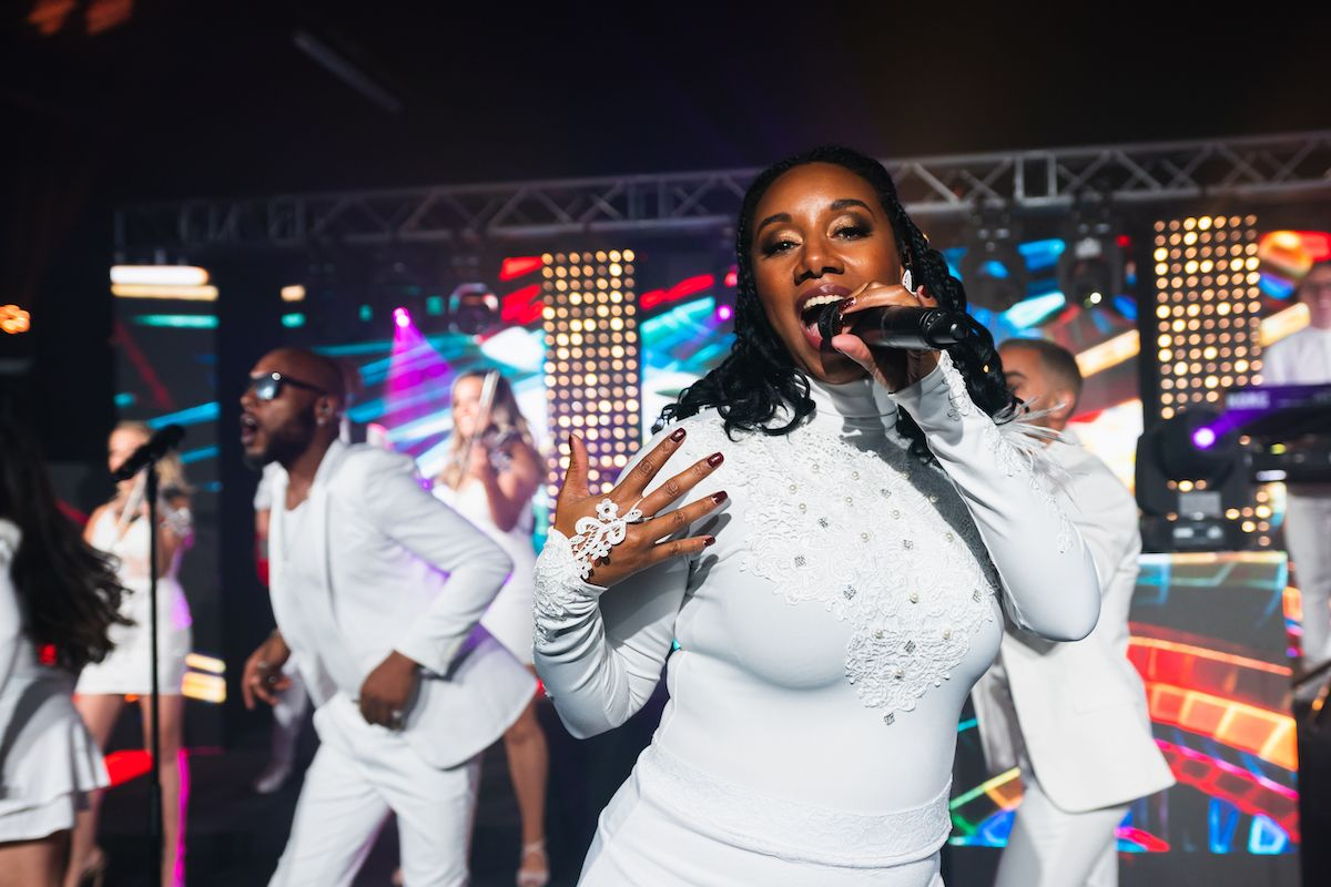 Jam Hot singer performing We Are Family, dressed all in white