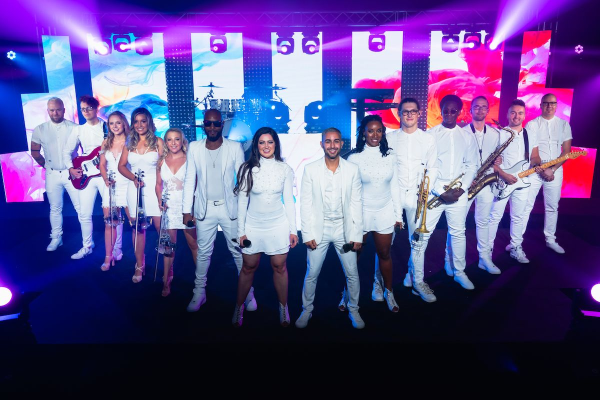 Jam Hot wearing Ice White outfits standing in a V formation
