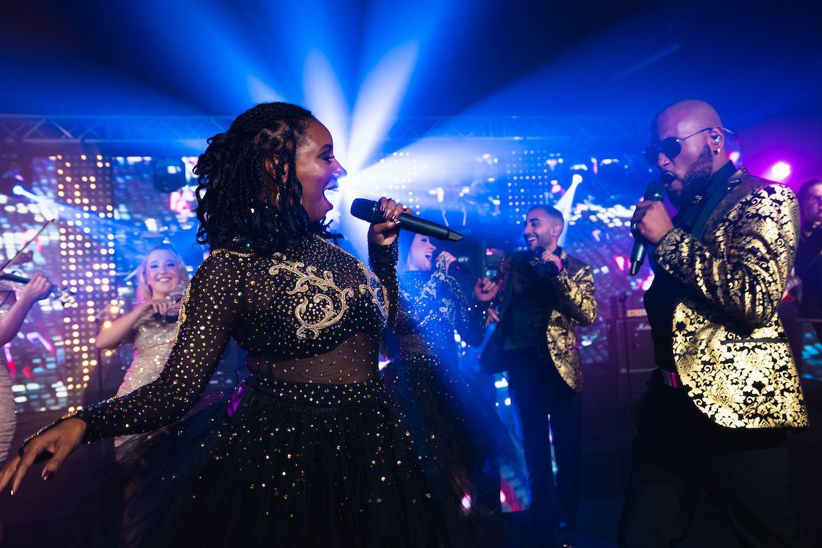 Jam Hot singers having fun on stage wearing dapper gold