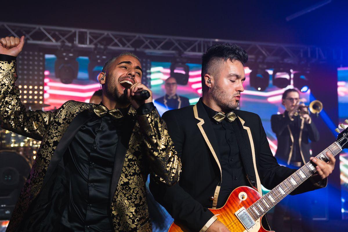 Jam Hot singer & guitarist on stage wearing dapper gold
