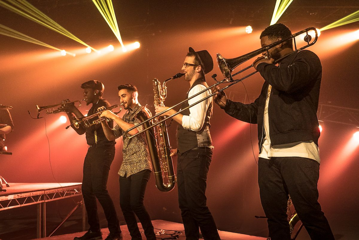 Jam Hot Horn section on stage, with orange beam lights