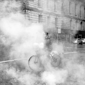 Man biking on a foggy urban street