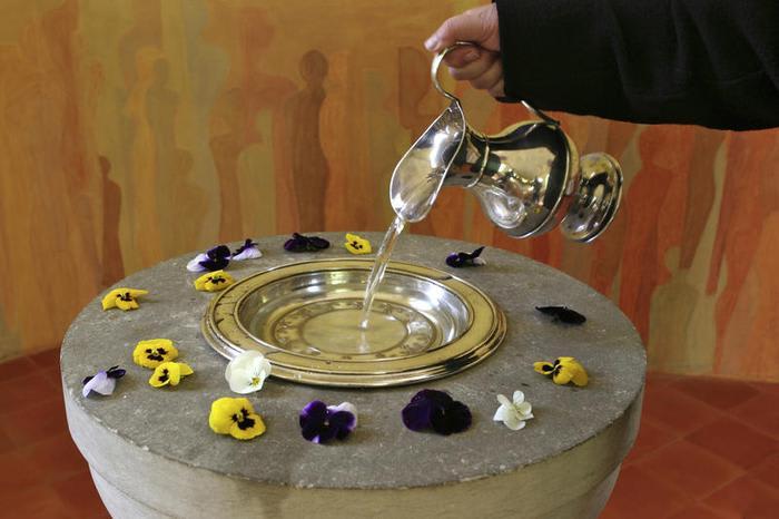 Taufe Taufbecken mit Wasser und Blüten