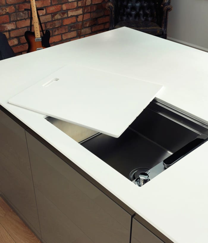Sliding a cover manually over the kitchen sink to make it invisible.
