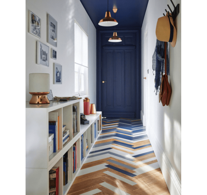 Entryway with blue painted door and ceiling. The same colour is tied into the floor tiles.