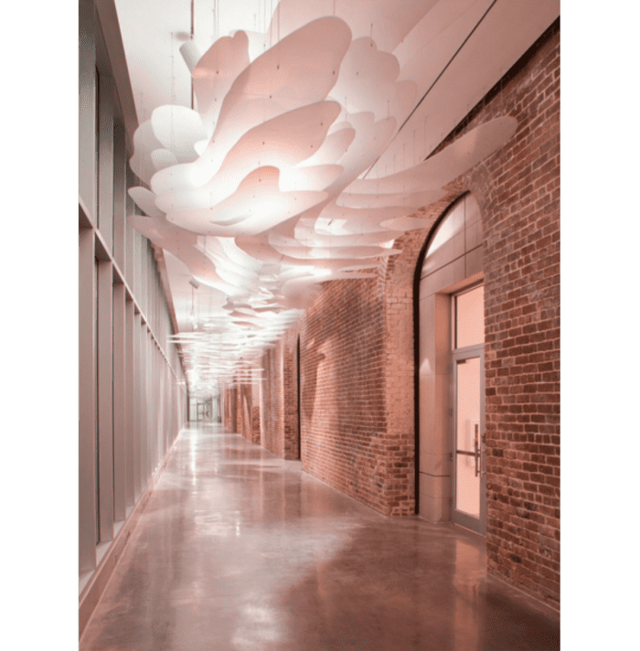 Corridor with white flat suspension lamps covering the ceiling completely.