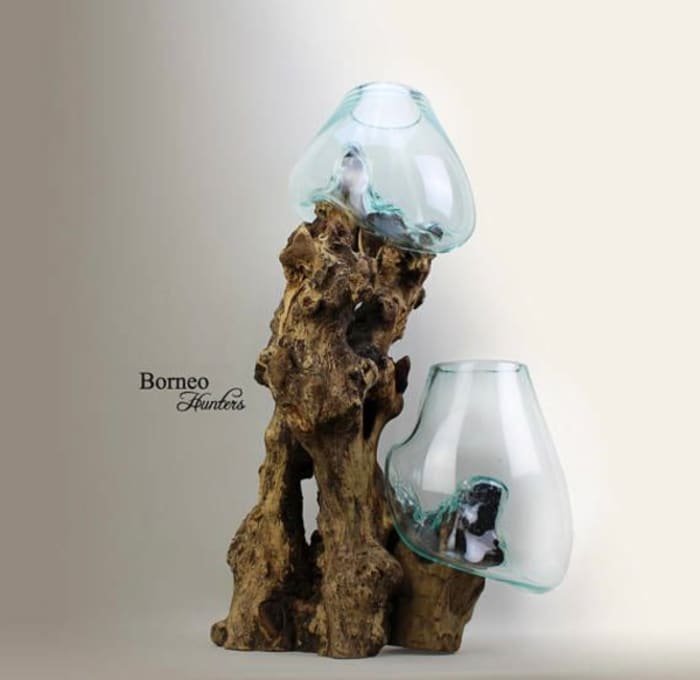 Planter made of a wood root as a base and hand blown glass vases that seem poured of top of the wood and take its shape.