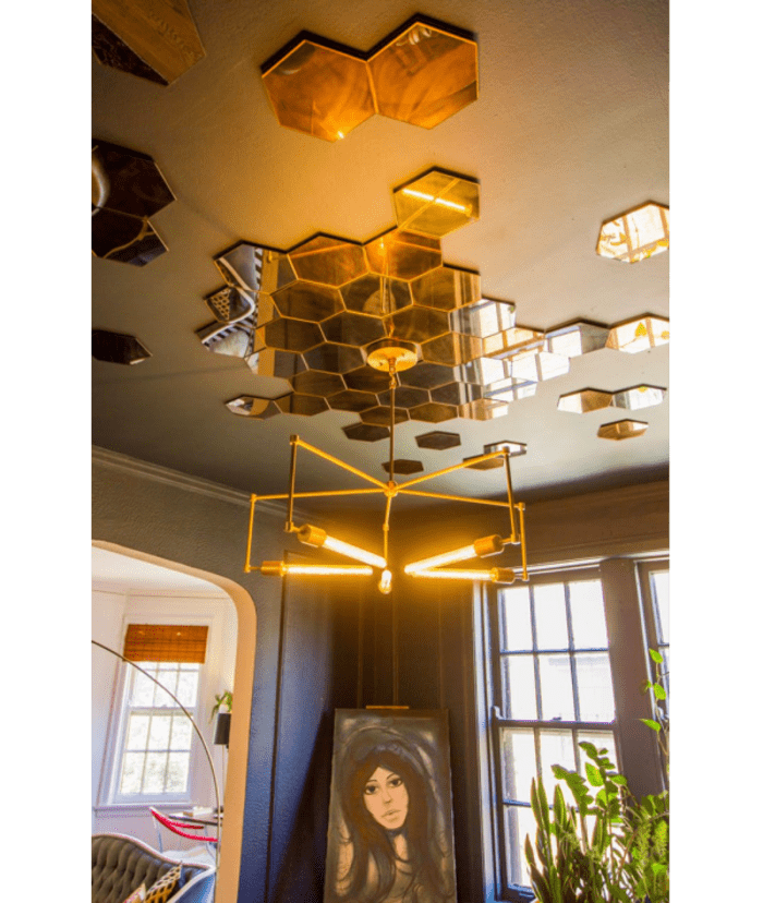 Dark blue ceiling with hexagonal mirror tiles disposed irregularly, creating a backdrop for the pendant light.