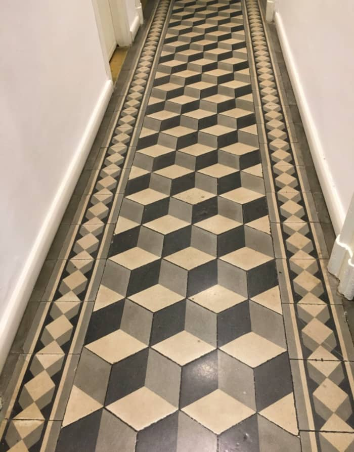 Period building corridor, tiled with a very modern black and white graphic pattern.