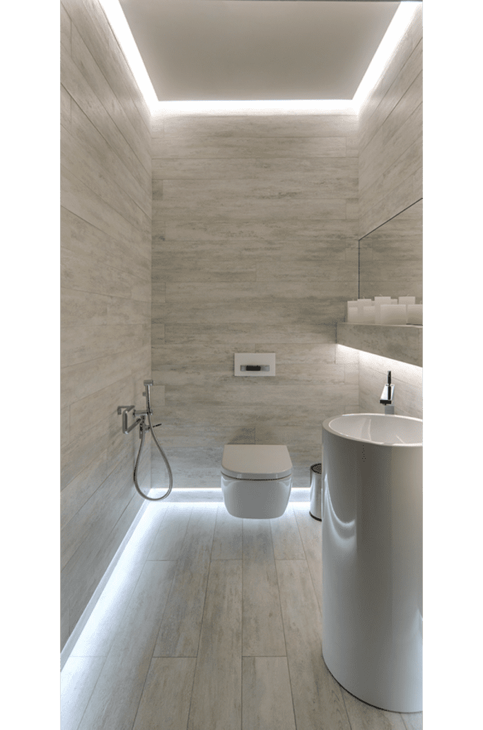 Bathroom with light running all around the perimeter of the room. The lighting body is hidden so all is visible is a light aura.