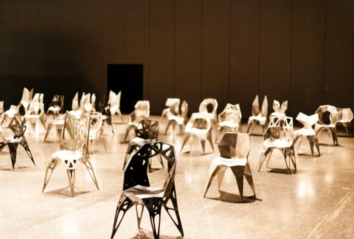 The fifty chairs displayed at the entrance of the fair