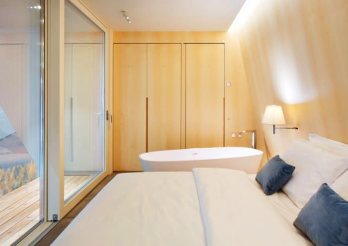 The interior of EDEN luxury portable suite, an example of sustainable living and energy efficiency. View of bed, bathtub and hidden storage wall.